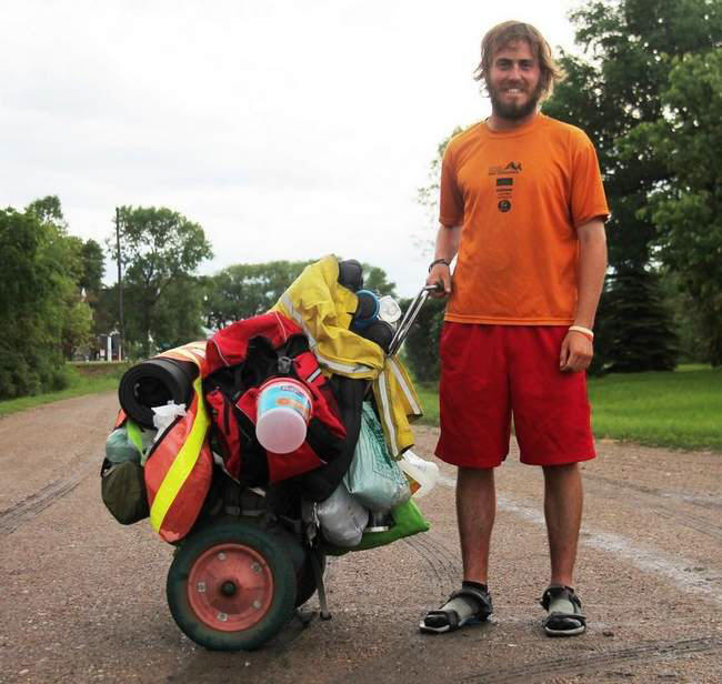 Andrew Seiss is photographed Monday evening at John Reitmeier's home north of Crookston, where he spent the night. He pushes a cart that is packed with all of the supplies he needs. He says the cart with given to him while walking in Kazakhstan.
